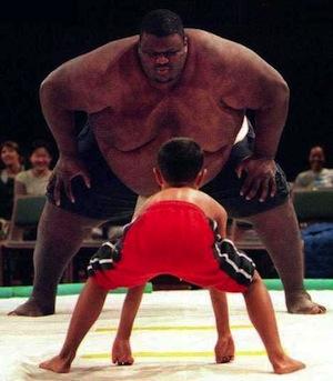 Big sumo facing a child